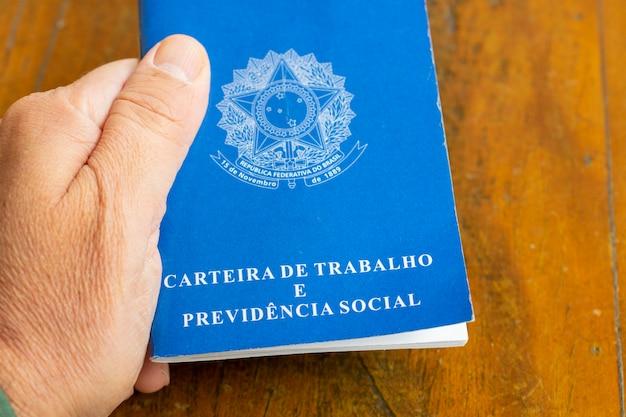 Carteira de trabalho brasileira. mão segurando a placa de trabalho na mesa de madeira rústica.