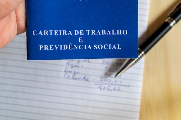 Carteira de trabalho brasileira. mão segurando o cartão de trabalho em fundo de papel branco com caneta e despesas mensais.