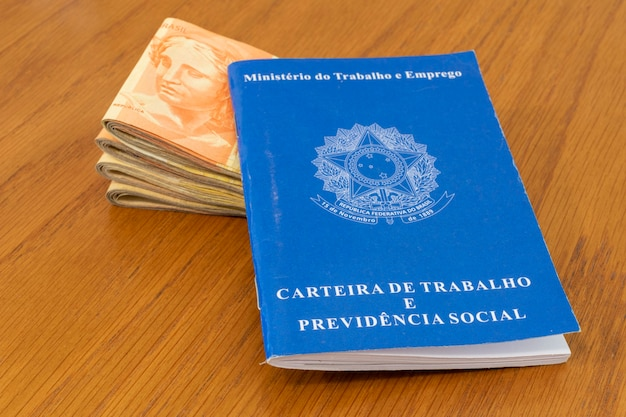 Carteira de trabalho com dinheiro brasileiro nota aumento de salário mínimo