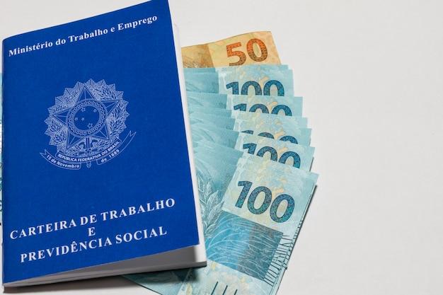 Carteira de trabalho no meio da moeda brasileira com espaço para texto
