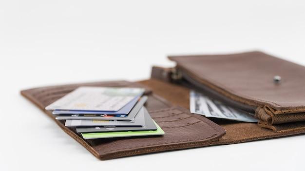 Carteira marrom com cartões de crédito e notas de cem dólares em fundo branco