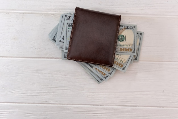 Carteira masculina de couro escuro com notas de dólar completas como base financeira, conceito de economia