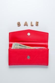 Carteira na moda vermelha na superfície branca com venda de texto.