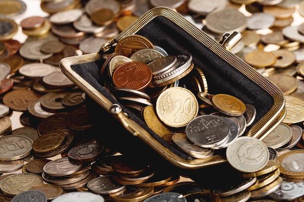Carteira preta com moedas diferentes. grande pilha de moedas brilhantes