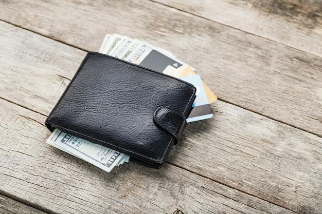 Carteira preta com notas, cartões eletrônicos e bitcoins em uma parede de madeira. símbolo de prosperidade e prosperidade.