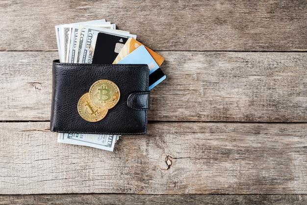 Carteira preta com notas, cartões eletrônicos e bitcoins na madeira.