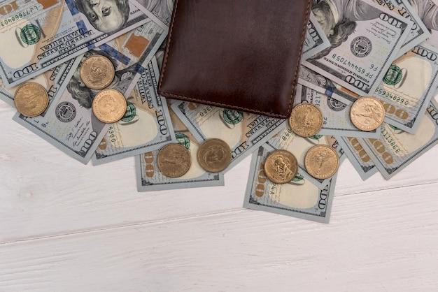 Carteira preta com notas de dólar e moedas de centavo, conceito de poupança Foto Premium