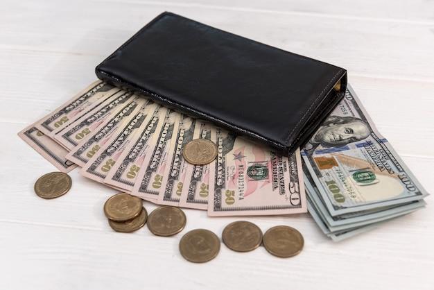 Carteira preta com notas de dólar e moedas de centavo, conceito de poupança