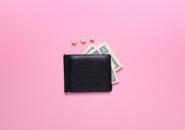 Carteira preta em um fundo rosa com o imposto de palavra de letras de madeira. vista superior, minimalismo