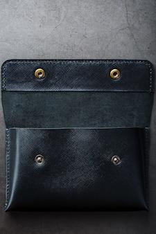 Carteira preta feita de couro genuíno no escuro