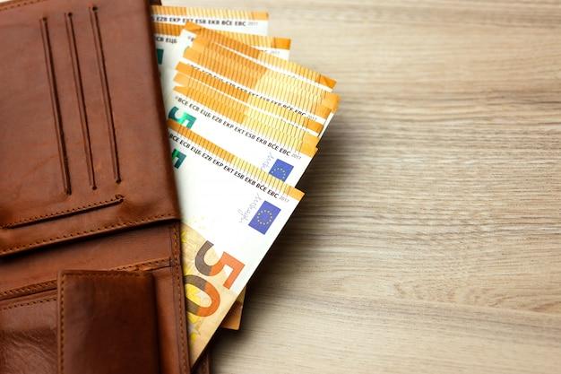 Carteira recheada com notas de euro no fundo de madeira