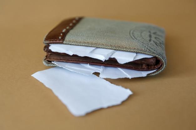 Carteira vazia com pedaços de papel em um fundo liso