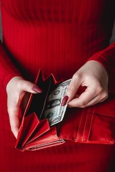 Carteira vermelha nas mãos de uma mulher em um vestido vermelho com manicure vermelha