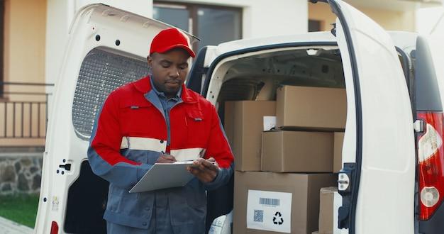 Carteiro americano africano no uniforme vermelho e boné em pé na van branca com caixas da caixa e preenchimento de documentos na área de transferência. ao ar livre.