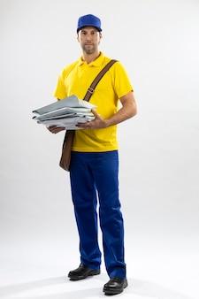Carteiro brasileiro em um fundo branco entregando um pacote. copie o espaço.
