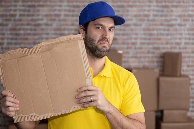 Carteiro brasileiro segurando uma placa em branco em um depósito com várias caixas. copie o espaço.