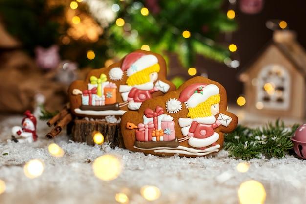 Carteiro de gengibre duas chirstmas e trenó com presentes em uma decoração aconchegante e quente com luzes de guirlanda