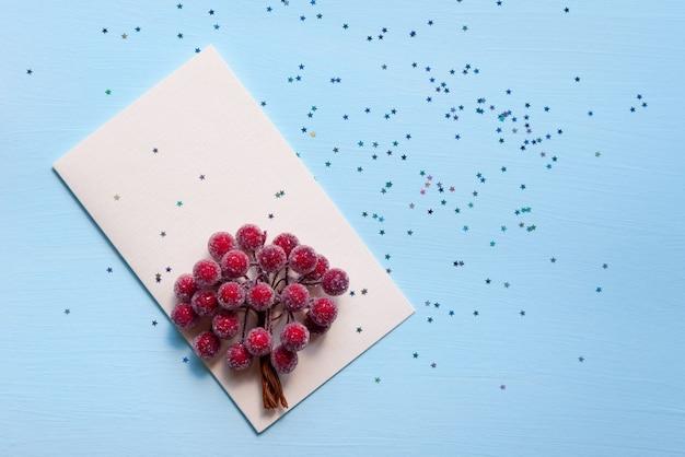 Cartões bege claros sobre um fundo azul com estrelas brilhantes e bagas ornamentais. decoração para o natal e ano novo.