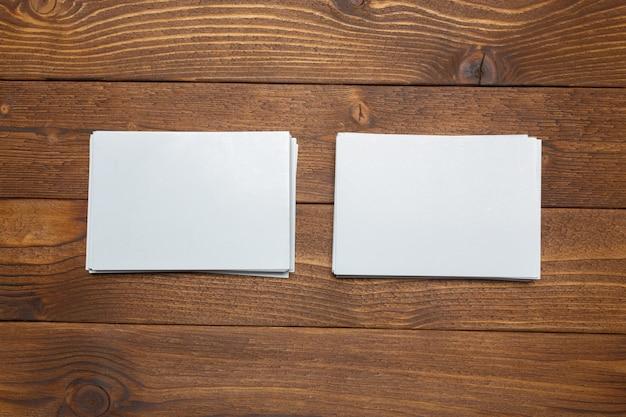 Cartões brancos em branco sobre fundo de madeira.