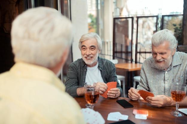 Cartões com amigos. homem barbudo idoso rindo enquanto jogava cartas com amigos sentados do lado de fora do bar