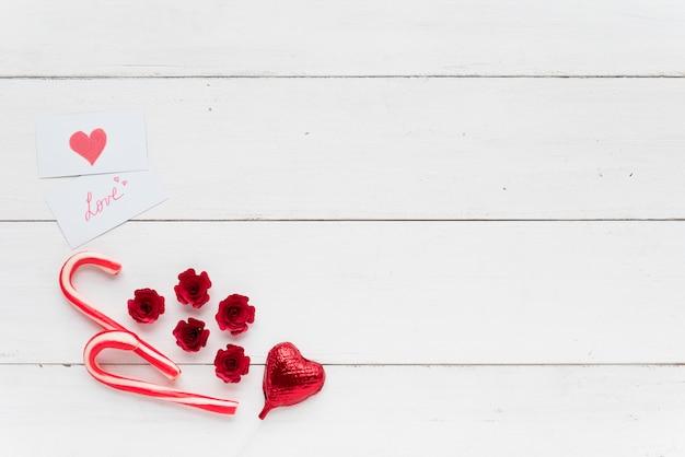 Cartões com inscrição de amor perto de coração decorativo e bastões de doces