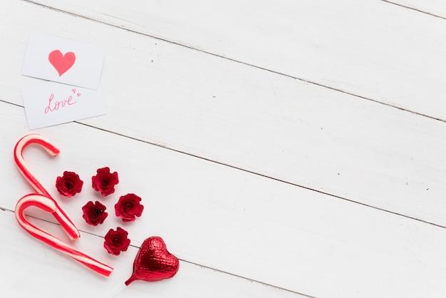 Cartões com título de amor perto de coração decorativo e bastões de doces