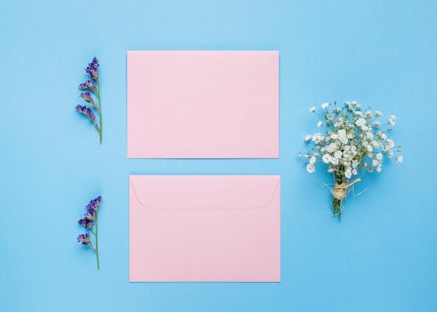 Cartões de casamento plana leigos ao lado de flores