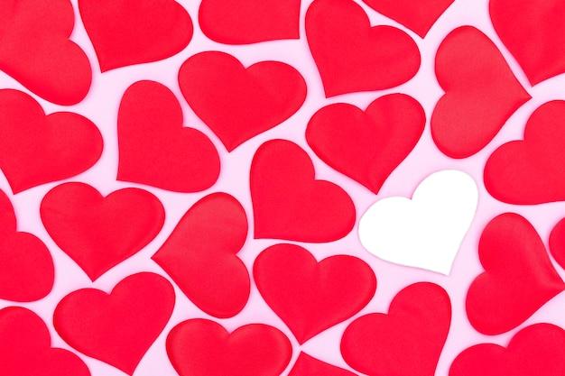Cartões de celebração em fundo rosa, um cartão decorado com corações vermelhos padrão, dia dos namorados