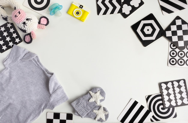 Cartões de contraste do desenvolvimento da visão. acessórios neutros unisex do bebê no fundo branco. vista plana leiga, superior. copie o espaço