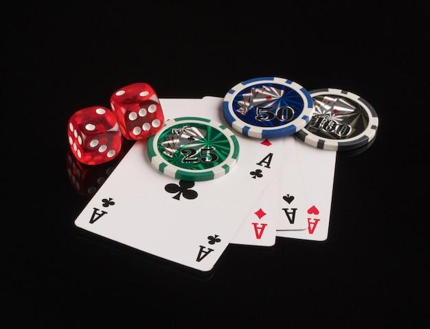 Cartões de fichas de pôquer e dados em um fundo preto o conceito de jogos de azar e entretenimento