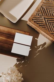 Cartões de folha de papel em branco, bandeja de madeira, caixão e flores secas com sombras de luz solar em bege