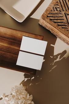Cartões de folha de papel em branco com bandeja de madeira, caixão e flores secas com sombra de luz solar em bege