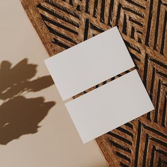 Cartões de folha de papel em branco com caixão de madeira e sombra de luz do sol de flores secas em bege