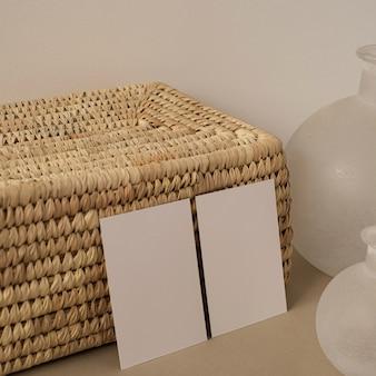 Cartões de folha de papel em branco com caixão de vime contra uma parede branca neutra.