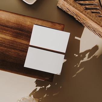 Cartões de folha de papel em branco com espaço de cópia, bandeja de madeira, caixão e flores secas com sombra de luz solar em bege