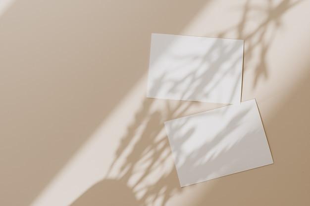 Cartões de folha de papel em branco com espaço de cópia com sombra de luz do sol em bege