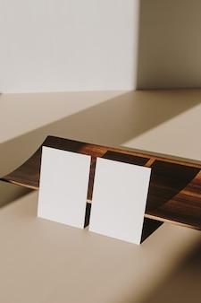 Cartões de folha de papel em branco com espaço de cópia e bandeja de madeira com sombra de luz do sol em bege