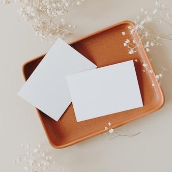 Cartões de folha de papel em branco com espaço de cópia e buquê de flores de gipsófila em bege neutro. camada plana, vista superior.