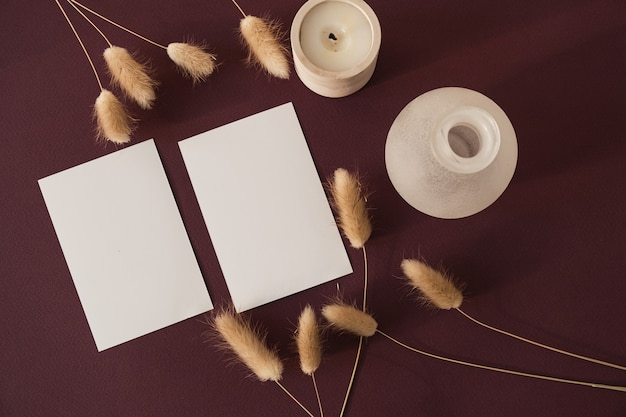 Cartões de folha de papel em branco com espaço de cópia e grama de cauda de coelho coelho nas sombras da luz do sol em borgonha