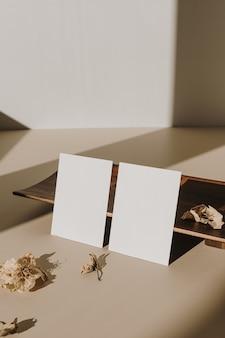 Cartões de folha de papel em branco com espaço de cópia vazio e bandeja de madeira, flores secas com sombras de luz solar em branco