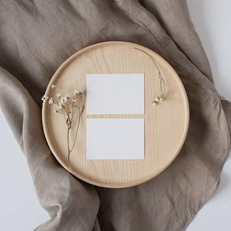 Cartões de folha de papel em branco com flores secas em caixão de madeira e cobertor de linho cinza