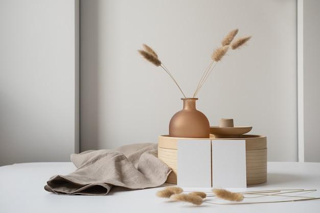 Cartões de folha de papel em branco com grama rabo de coelho, caixão de madeira e cobertor de linho cinza.