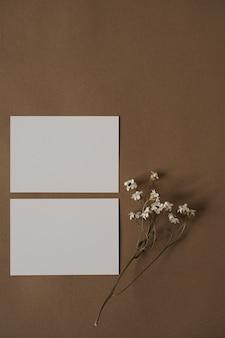 Cartões de folha de papel em branco com lindas flores brancas em marrom neutro