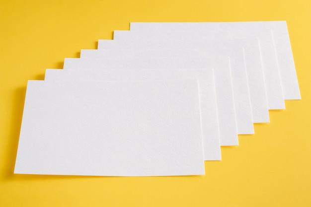 Cartões de folhas vazias de papel branco sobre um fundo amarelo