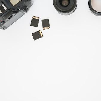 Cartões de memória; lente da câmera e câmera digital dslr profissional no fundo branco