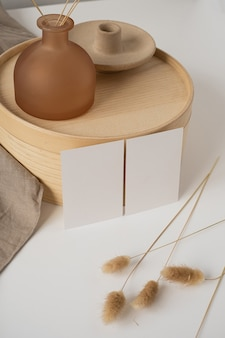Cartões de papel em branco com grama rabo de coelho, bandeja de madeira, cobertor bege neutro.