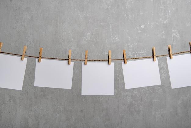 Cartões de papel em branco pendurados com prendedores de roupa na corda em fundo cinza. copie o espaço. lugar para o seu texto.