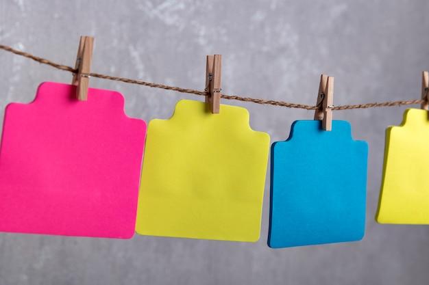 Cartões de papel varicoloured em branco pendurados com prendedor de roupa na corda. copie o espaço. lugar para o seu texto.