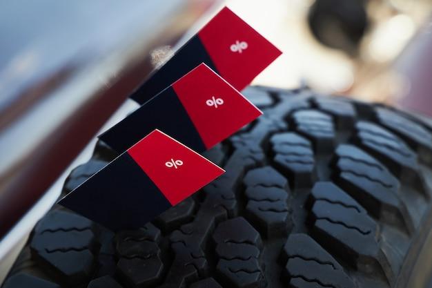 Cartões de papelão com desconto percentual escrito na compra de pneus de carro