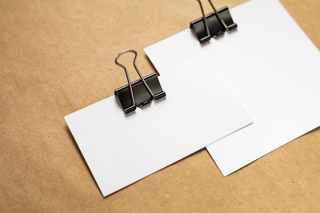 Cartões de visita brancos combinados com um clipe de papel em um fundo de papel kraft. vista do topo. copie o espaço
